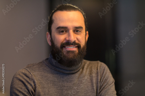 smiling middle eastern man in polo neck sweater