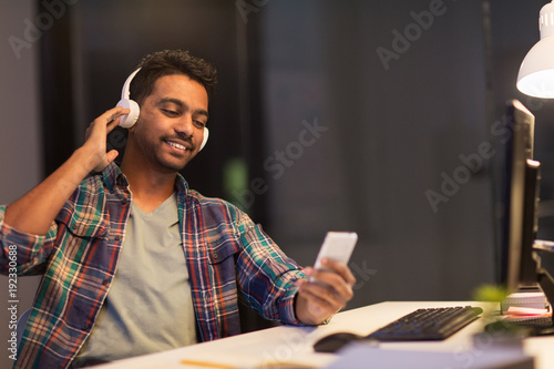 man with headphones and smartphone at night office