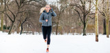 Woman running or jogging down a path on winter day in park - 192333287