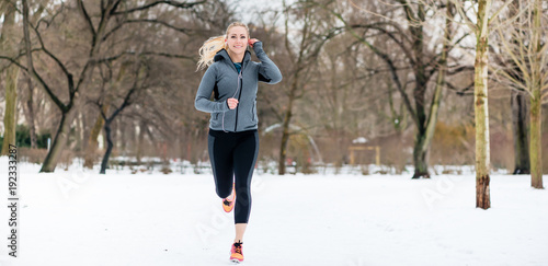 Fototapeta Woman running or jogging down a path on winter day in park