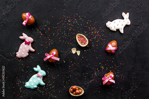 Easter candy. Traditional Easter signs and symbols. Chocolate Easter eggs and Easter bunny cookies. Black background top view