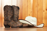 cowgirl embroidered boots and white hat on wooden background - text space - 192334429