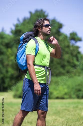 Young man hiking at green nature
