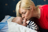 Young blonde mom kissing her baby    - 192348214