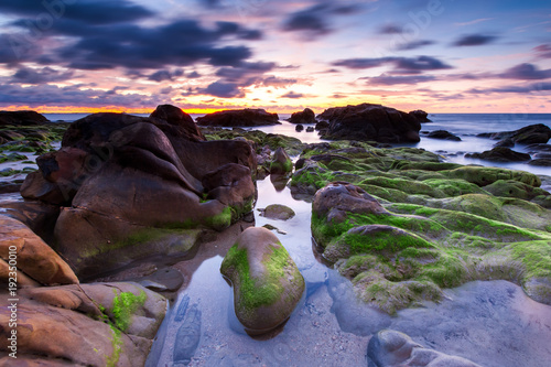 Foto op Plexiglas Chocoladebruin sunset seascape with natural coastal rocks by the beach.