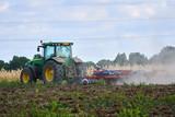 Tractor harrowing the field - 192353271