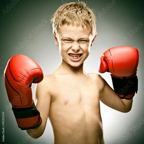 young angry boy play boxe with gloves portrait on grey background