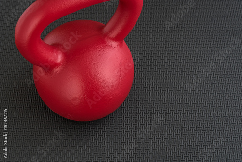 Close up of a red kettle bell on a textured black floor