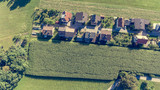 Drop down view of rural houses next to corn field. - 192372813
