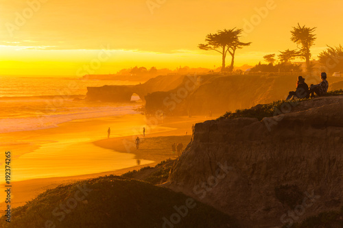 People enjoying the view of a stunningly colorful sunset in Santa Cruz, California in winter