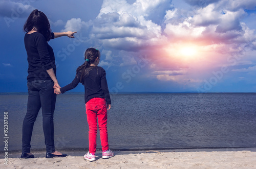 young mother with her daughter on the beach