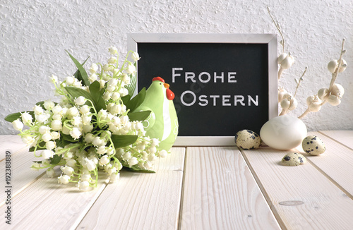 Fotobehang Lelietjes van dalen Blackboard decorated with ceramic hen, eggs and and lily of the valley flowers, text