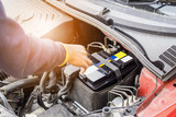 car mechanic use voltmeter to check car battery voltage level