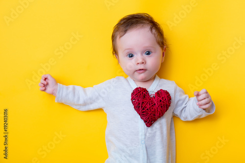 little baby with red heart shape toy