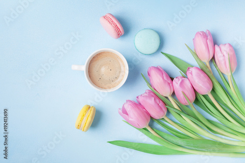 Fototapeta Spring tulip flowers, colorful macaroons and coffee on blue pastel table top view. Beautiful breakfast on Mothers or Womans day. Flat lay.