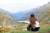 girl with a backpack sits with her back near the cliff, mountain view