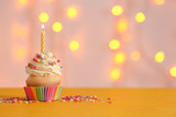 Birthday cupcake with candle on table against blurred lights - 192419052