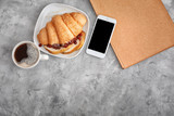 Tasty croissant with cup of coffee and mobile phone on table - 192420070