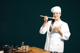 Beautiful female chef tasting salad on color background - 192420220