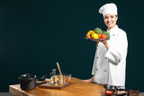 Beautiful female chef holding plate with vegetables near table on color background - 192420221