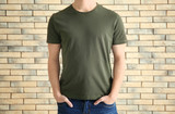 Young man in stylish t-shirt against brick wall. Mockup for design - 192420409