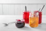 Jars with sweet jams on table - 192420437