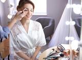 Makeup artist preparing bride before her wedding in room - 192420461