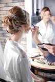 Makeup artist preparing bride before her wedding in room - 192420462