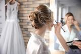 Makeup artist preparing bride before her wedding in room - 192420464