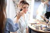 Makeup artist preparing bride before her wedding in room - 192420466