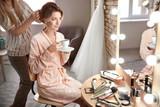 Hairdresser preparing bride before her wedding in room - 192420474