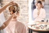 Hairdresser preparing bride before her wedding in room - 192420475