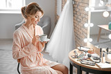 Beautiful young bride drinking coffee in makeup room - 192420487