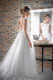 Beautiful young bride in white wedding dress with makeup created by professional artist near mirror indoors - 192420490