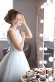 Beautiful young bride in white wedding dress with makeup created by professional artist near mirror indoors - 192420499