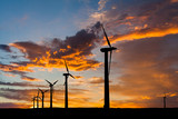 Big wind turbines in the desert at sunset background