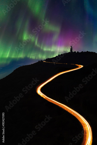 Fotobehang Noorderlicht Night road in the mountains against the background of the Northern Lights