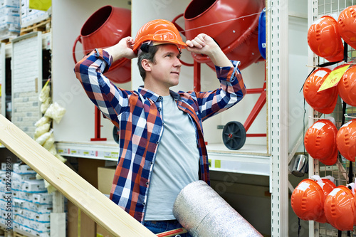 Man chooses and buys construction helmet in store