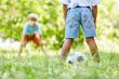 Zwei Kinder spielen Fußball zusammen