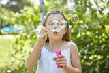 Mädchen pustet Seifenblasen im Sommer - 192431008