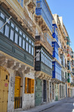 Fototapeta  - a narrow street with picturesque and colorful tenement houses in Malta © karolinaklink