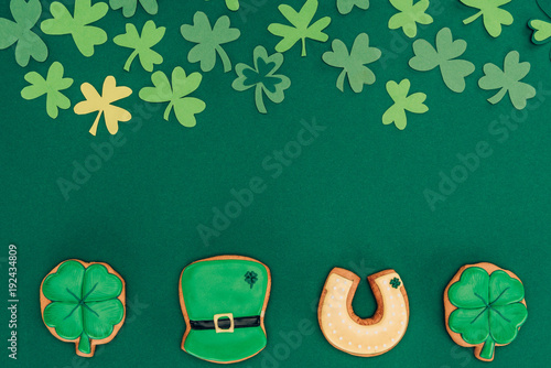 top view of icing cookies and paper shamrock isolated on green, st patricks day concept