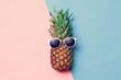 Quadro pineapple on colored paper with glasses
