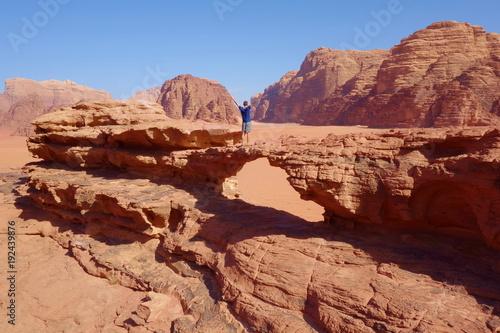 Papiers peints Saumon Young man standing at natural rock bridge and panoramic view of Jordanian desert Wadi Rum