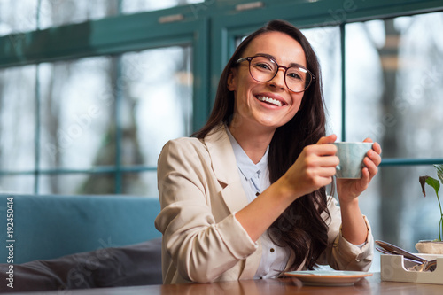 Sincere smile. Good looking positive energetic woman sitting at the table while laughing and tasting coffee