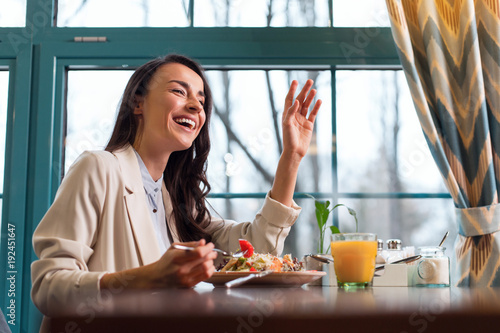 Bill please. Joyful good looking young woman tasting salad while rising hand and laughing - 192451647