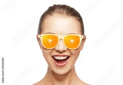 happy teenage girl in sunglasses with oranges