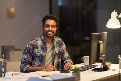 creative man with tablet pc at night office