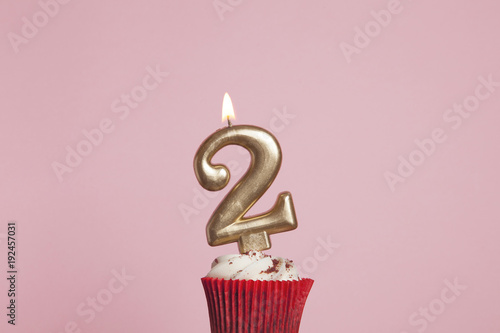 Number 2 Gold Candle In A Cupcake Against Pastel Pink Background
