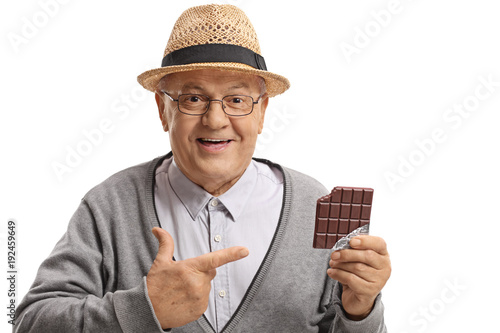 Mature man holding a chocolate bar and pointing